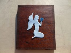 white enamelled fairy on wooden board