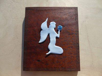 white enamelled fairy on wooden board