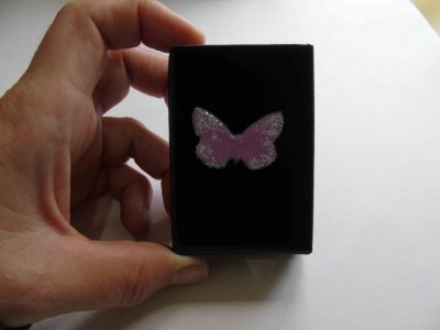pink butterfly brooch with white on wing tips