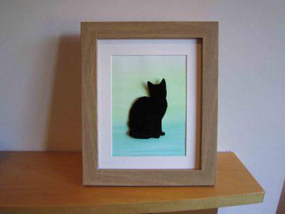 enamelled black cat in frame