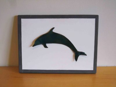 turquoise enamelled dolphin on painted wooden board