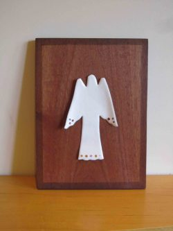 White enamelled angel on wooden board