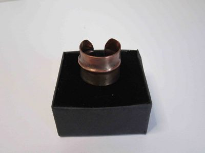 Fold formed copper ring resting on presentation box