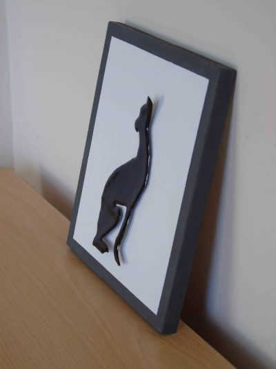 Side view of enamelled greyhound on painted wooden board