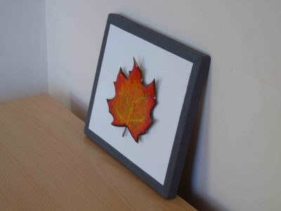 side view of enamelled leaf on painted wooden board
