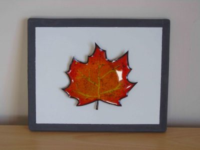 enamelled leaf on painted wooden board