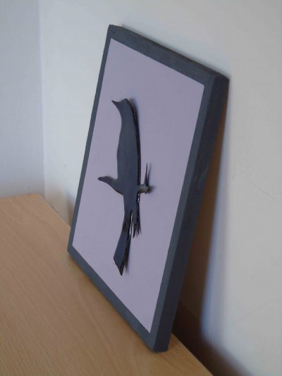 side view of enamelled blackbird on painted wooden board