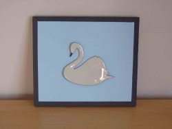 White enamelled swan on blue wooden board