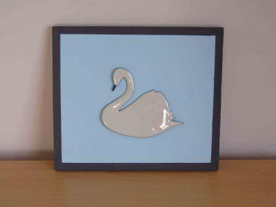 White enamelled swan on blue wooden board