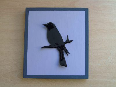 Black blackbird silhouette on mauve wooden frame