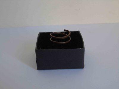 dark narrow spiral copper ring resting on its box