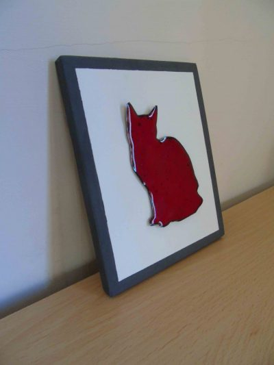 Enamelled red cat wall hanging from the side