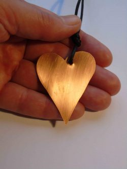 Copper heart necklace being held
